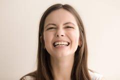 Gevoelsheadshotportret van lachende jonge vrouw stock foto