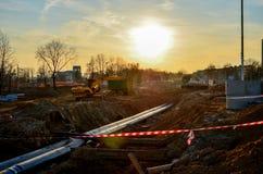 Gevolgd graafwerktuig met een emmer in de grond bij een bouwwerf tijdens het leggen van rioolpijpen in de grond stock afbeeldingen