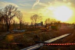 Gevolgd graafwerktuig met een emmer in de grond bij een bouwwerf tijdens het leggen van rioolpijpen in de grond royalty-vrije stock afbeelding