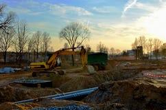 Gevolgd graafwerktuig met een emmer in de grond bij een bouwwerf tijdens het leggen van rioolpijpen in de grond royalty-vrije stock foto's