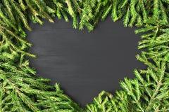 Gevormd die het hart van het Kerstmiskader van natuurlijke spar wordt gemaakt vertakt zich op zwarte houten achtergrond Vlak leg, stock foto