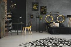 Gevormd tapijt in het binnenland van de tiener` s ruimte met gele stoel a stock foto