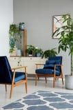 Gevormd tapijt naast blauwe leunstoelen in grijs flatbinnenland met installaties op kabinet stock fotografie