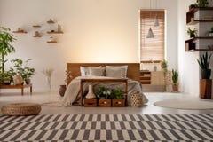 Gevormd tapijt voor bed in botanisch slaapkamerbinnenland met installaties en venster Echte foto stock afbeeldingen