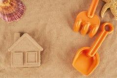 Gevormd zandhuis en plastic speelgoed, die op het strand leggen stock foto