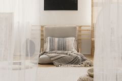 Gevormde hoofdkussen en deken op beige futon in artistieke slaapkamer binnenlandse, echte foto royalty-vrije stock afbeeldingen