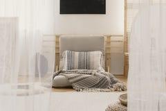 Gevormde hoofdkussen en deken op beige futon in artistieke slaapkamer binnenlandse, echte foto stock fotografie