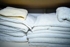 Gevouwen die handdoeken binnen een linnenkast worden gestapeld stock foto