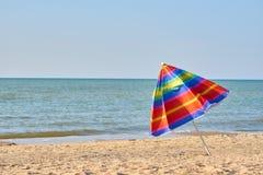 Gevouwen gekleurde strandparaplu op het strand Het sluiten van het vakantieseizoen royalty-vrije stock foto
