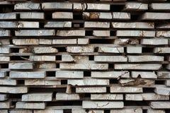 Gevouwen houten bruine en grijze planken in een zaagmolen stock foto