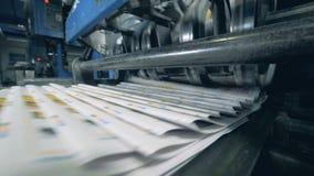 Gevouwen krant op een geautomatiseerde riem, typografische machine stock footage