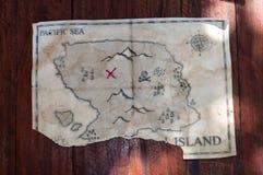 Gevouwen Uitstekende valse kaart van abstract eiland en rood kruis van Schatborst op houten lijst Royalty-vrije Stock Foto