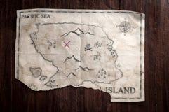 Gevouwen Uitstekende valse kaart van abstract eiland en rood kruis van Schatborst op houten lijst Stock Foto
