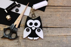Gevuld gevoeld uilstuk speelgoed, zwart-witte gevoelde bladen, schaar, draden, knopen op een uitstekende houten achtergrond met e Stock Foto