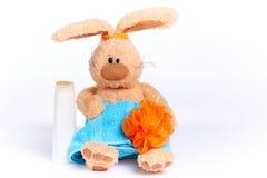 Gevuld zacht konijn in een blauwe handdoek met een rubber op de oren en met douchetoebehoren royalty-vrije stock afbeelding