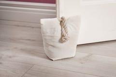 Gevulde zak die houten deur houden stock foto