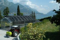 Gewächshaus und Traktor mit schöner Landschaft Lizenzfreies Stockfoto