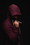 Gewöhnen Sie Mann in einer Haube mit einer Spritze, die vom roten flüssigen Heroin auf einem schwarzen Hintergrund voll ist Droge Stockfotografie