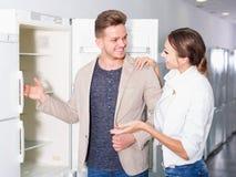 Gewöhnliche junge Kunden, die Kühlschränke betrachten Stockbild