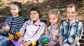 Gewöhnliche Kinder im Park auf einer Bank im Herbst stockbilder