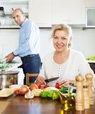 Gewöhnliche reife Paare, die Lebensmittel mit Gemüse kochen Stockfoto