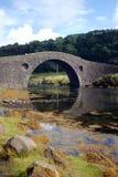 Gewölbte Steinbrücke über Fluss lizenzfreie stockfotografie