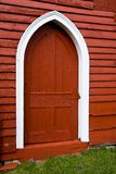 Gewölbte Tür im alten roten hölzernen Stall. Stockfoto