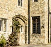 Gewölbte Tür und verbleite Fenster eingestellt in Stein. Lizenzfreie Stockfotos