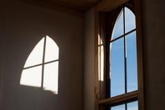 Gewölbtes Fenster und seine Reflexion auf dem Innenraum eines Altbaus Lizenzfreie Stockfotos