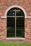 Gewölbtes Glasfenster auf brauner Backsteinmauer Stockfoto