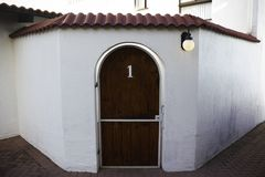 Gewölbtes hölzernes Front Gate Number One To-Gericht mit Toskana-Art-Architektur stockbild