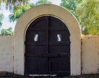 Gewölbtes Tor des luftgetrockneten Ziegelsteines mit Holztür in Kalifornien Lizenzfreie Stockfotos