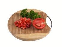 Gewürfelte Tomaten auf einem hölzernen Brett lokalisiert Stockfotografie