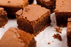 Gewürfeltes Backpapier der Schokolade Schokoladenkuchen auf einem Holztisch Stockfoto