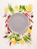 Gewürz und Gewürze um leeres graues plateon weißen hölzernen Hintergrund, Draufsicht, Stockbild