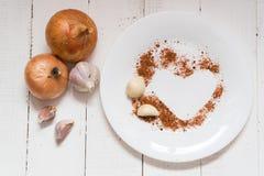 Gewürze auf einer Platte Knoblauchzwiebel-Pfeffergewürze in Form eines Herzens stockfoto