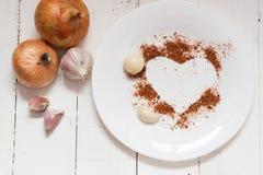 Gewürze auf einer Platte Knoblauchzwiebel-Pfeffergewürze in Form eines Herzens stockfotografie
