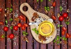 Gewürze, Kirschtomaten, Basilikum und Pflanzenöl auf dunklem Holztisch, Draufsicht stockbild