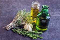 Gewürze, Kräuter und Knoblauch, Olivenöl nahe bei einer Flasche Stockfoto