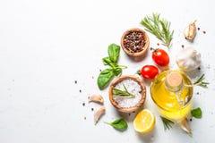 Gewürze, Kräuter und Olivenöl über weißer Steintabelle stockbild