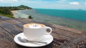 Gewürzter Kaffee in der weißen Schale auf Platte mit Löffel auf hölzerner rustikaler Tabelle, Seehintergrund mit der Palme, die h stock footage