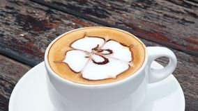 Gewürzter Kaffee in der weißen Schale auf Platte mit Löffel auf hölzerner rustikaler Tabelle, Wellenbewegung Trinkender Kaffee mi stock video