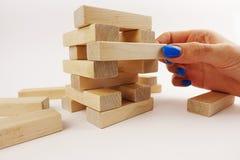 Gewaagd bewegingenconcept met vrouwenhand die een houten stuk van een toren vastspijkeren stock afbeelding