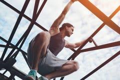 Gewaagde moedige mens die en op hoge metaalbrug beklimmen zitten stock foto's