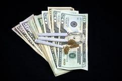 Gewaaid geld met marihuana op zwarte royalty-vrije stock foto