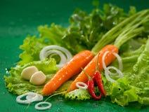 Gewaschene Karotten auf grünen Kopfsalatblättern, mit Knoblauch und rotem Paprika auf einem grünen Hintergrund Stockfoto