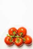 Gewassen rijpe tomatengroep op plaat op witte achtergrond, vertica Stock Foto
