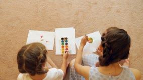 Gewassenvrouw en meisje die op papier trekken stock videobeelden