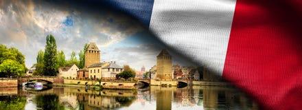 Gewebe-Flagge von Frankreich und von Straßburg-Stadtbild, Elsass, Frankreich Traditionelle Fachwerk- Häuser von Petite France lizenzfreie stockfotografie
