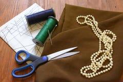 Gewebe, Perlen, Scheren, Kreide, Threads, Muster, Entwürfe Stockbild
